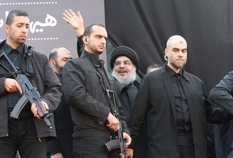 The head of Lebanon's militant Shiite Muslim movement Hezbollah, Hassan Nasrallah is surrounded by security guards as he greets the audience after giving a speech during a massive Shiite Muslim commemoration in southern Beirut on November 14, 2013. Nasrallah vowed to keep his forces in Syria where they are fighting alongside President Bashar al-Assad's regime, during his rare public speech.   AFP PHOTO/ STR